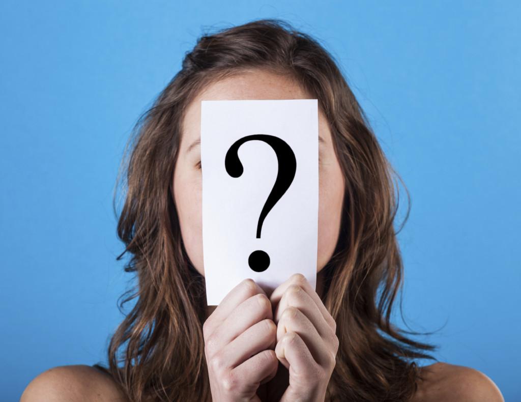 Woman Hiding Behind a Question Mark